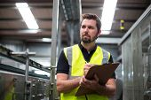 Attentive factory worker writing on clipboard in factory poster