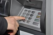 image of automatic teller machine  - Someone pressing number button on ATM machine - JPG