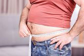 Adult man in t-shirt, jeans and tape-measure on blurred background. Weight loss concept poster