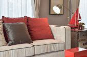 Classic Industrial Look Living Room With Beige Sofa And Red And Deep Brown Linen Pillows With Brass poster