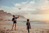 Father And Son Operating Drone By Remote Control At Beach poster