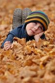 stock photo of prone  - 6 years old child lying prone in autumn leaves in a park - JPG