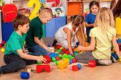 Children building blocks in kindergarten. Group kids playing toy on floor . Top view of interior pre poster