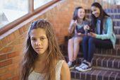 School friends bullying a sad girl in school corridor at school poster