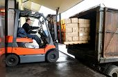 image of heavy equipment operator  - Electric forklift in warehouse loading cardboard boxes - JPG