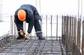 stock photo of formwork  - worker in workwear making reinforcement metal framework for concrete pouring - JPG