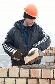 pic of pecker  - A brick layer worker building a brick wall at construction site - JPG