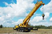 stock photo of boom-truck  - yellow automobile crane with risen telescopic boom outdoors over blue sky - JPG