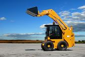 stock photo of skid-steer  - skid steer loader construction machine with bucket outdoors - JPG