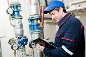 picture of boiler  - maintenance engineer checking technical data of heating system equipment in a boiler room - JPG
