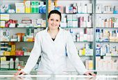 stock photo of antibiotics  - Happy cheerful pharmacist chemist woman standing in pharmacy drugstore - JPG