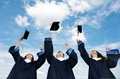 stock photo of graduation gown  - three graduate students tossing up hats over blue sky - JPG