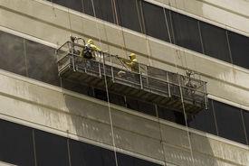 foto of pressure-wash  - Window washers washing windows on a high rise building - JPG
