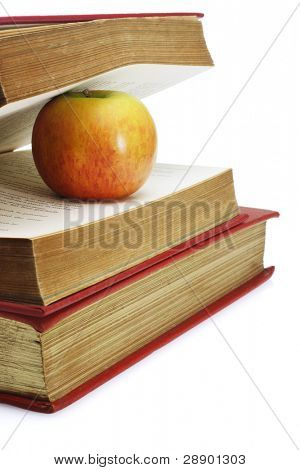 Red apple in between pages of old book on white background