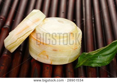 Opened jar of cream with fresh green leaf on bamboo mat with water droplets