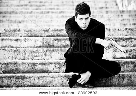 Young armed gun waiting on the steps
