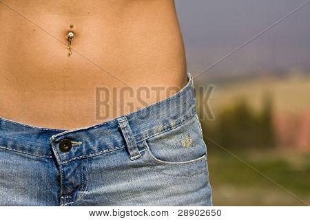 Woman abdomen in jeans detail.