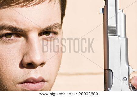 Close portrait of a man with a gun