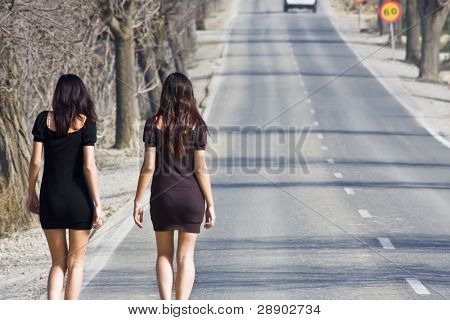 Two young women walking on the road