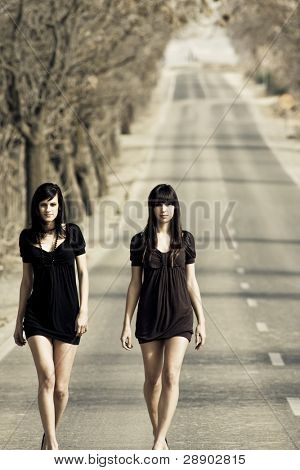 Two couple of young models parading in the middle of the road