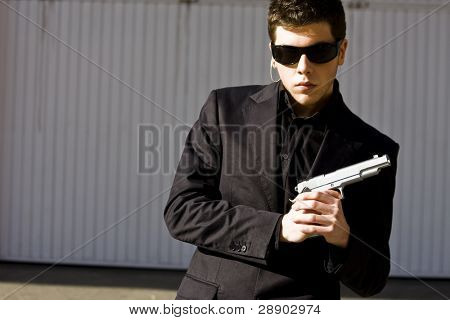 Male model performing secret agent with gun