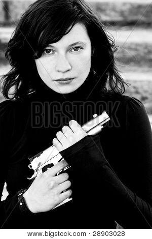 Black & white portrait of woman with a gun.