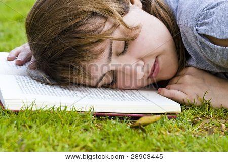 Joven rubia tomando una siesta después de la lectura