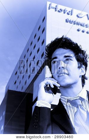 Businessman on phone over urban background, blue toned.