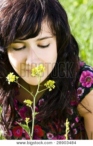 Young woman smelling yellow flower, green background