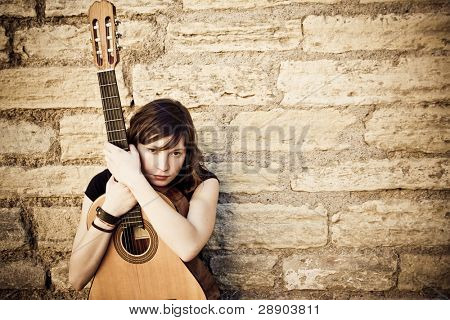 Young guitar performer against brickwall