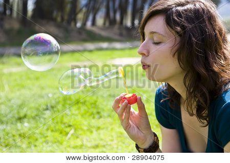 Young woman portrait making soap bubbles.