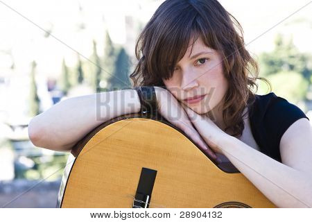 Young female guitar performer staring at camera