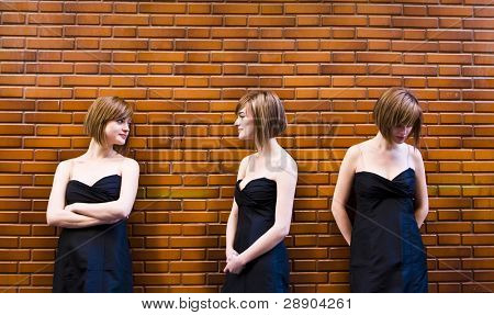 Cloned woman in different expressions over brickwall
