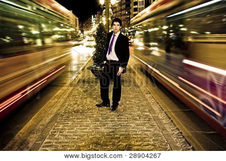 Businessman in night urban scenery, blurred motion.