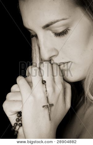 Young female prayer with rosary in sepia.