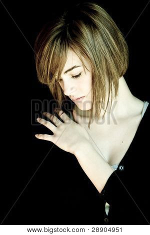 Sad blond woman portrait against black background