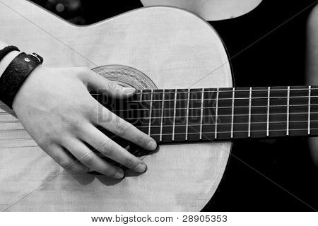 Hand on guitar, black and white.