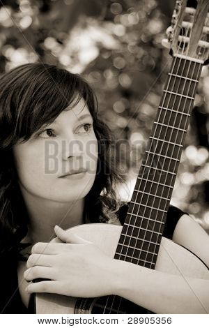 Young woman holding her classic guitar, sepia toned.
