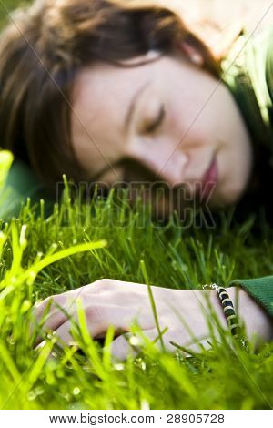 Young woman dreaming in the grass, focus on hand.