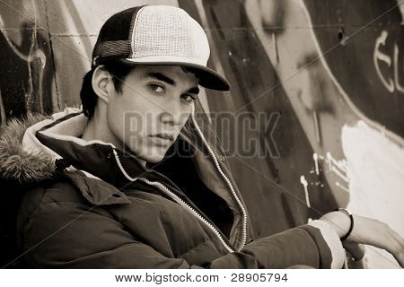 Young adolescent in casual clothing over grafted wall