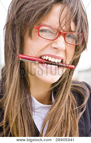 Young businesswoman in red glasses bitin a pen