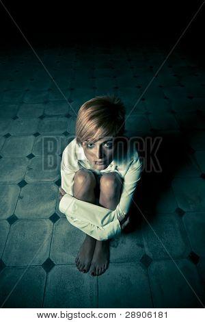 Junge blonde Frau, die allein in der Dunkelheit