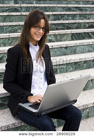 Young businesswoman staring at camera sited on stairs.