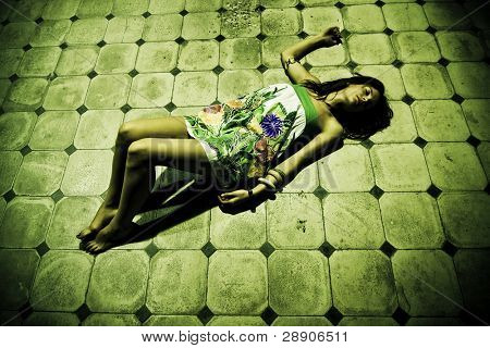 Woman laying in spooky floor with short dress.