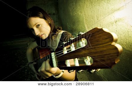 Young female guitarist in the dark