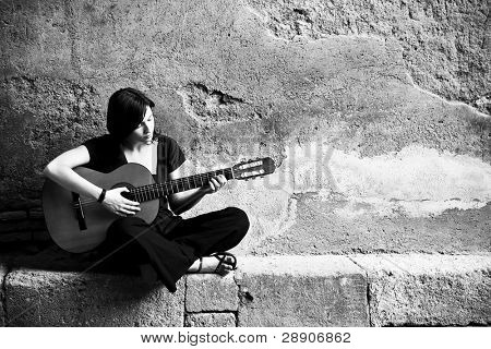 Lone sad guitarist playing in old brickwall.