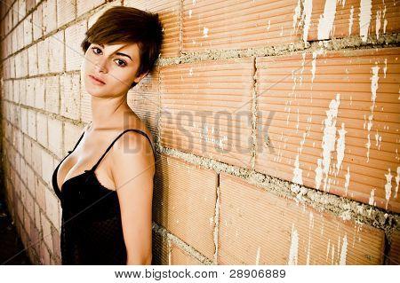 sexy gekleidete junge Frau auf schmutzigen Brickwall.
