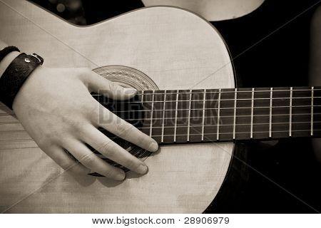 Hand auf Gitarre, alte Sepia toned.