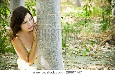 Young beautiful woman playing hide and seek in the trees.