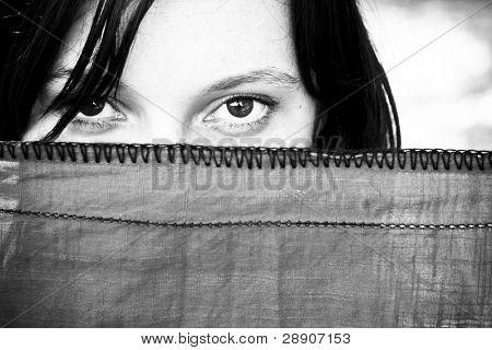 Young woman looking at camera behind veil.